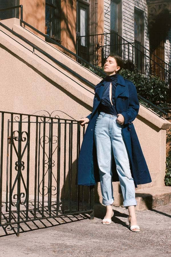 style blogger gabrielle arruda wearing navy trench caot with silk orseund iris blouse and taped jeans for timeless style outerwear pieces