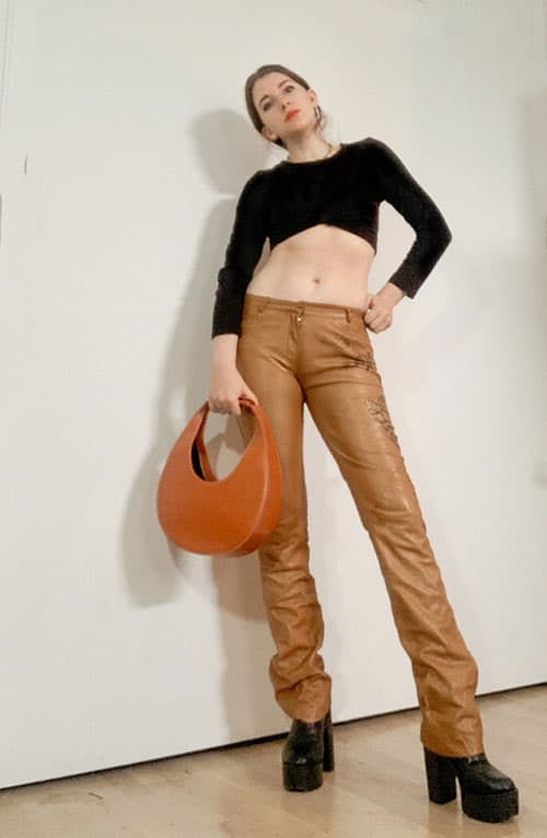 spring fashion trends 2021 low-rise pants. style blogger gabrielle arruda wearing low rise leather pants (light brown) with a black crop top and platform black boots