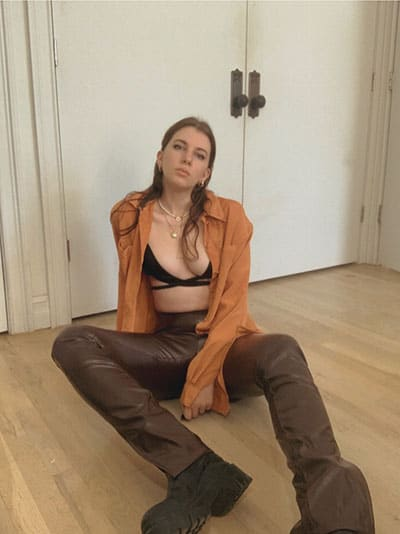 spring fashion trends 2021- split hem leather pants, fitted blouse (open) and a strappy bra top and chunky boots on style blogger gabrielle arruda