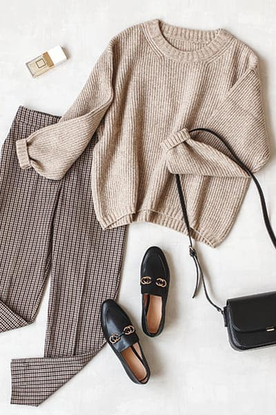 timeless style outfit flatlay- tan sweater with trousers, loafers, black crossbody,