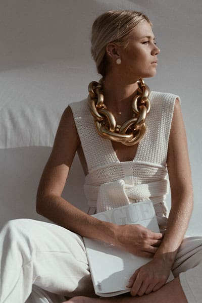 spring fashion trends 2021, elevated crochet and knits. woman in tie front crochet top with x-large gold chain and vogue magazine in her hand