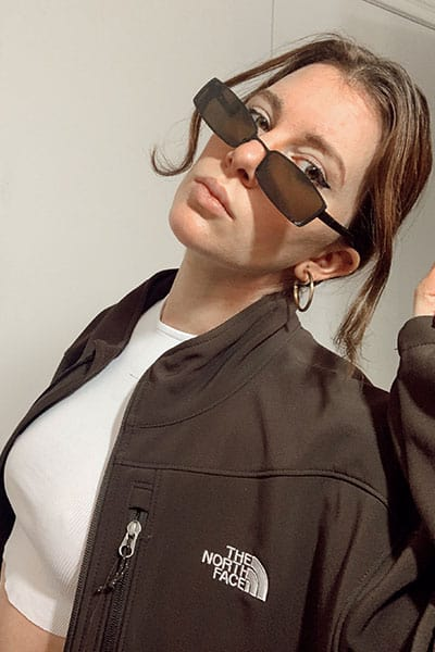 Gabrielle arruda wearing 90s matrix style sunglasses with brown windbreaker. spring fashion trends 2021