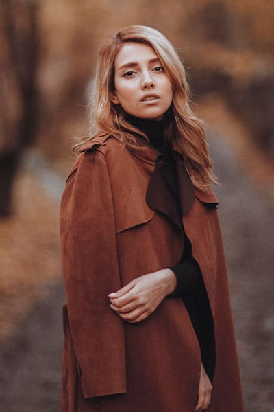 woman in brown trench coat with silk scarf, timeless style example