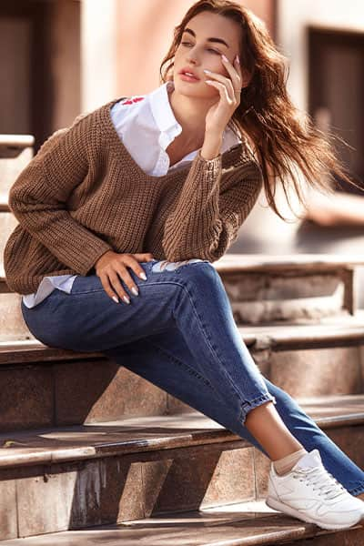 sophisticated woman in white blouse with tan knit sweater over with fitted jeans and white sneakers, exuding timeless style outfit idea