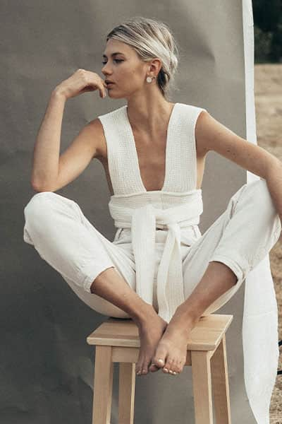 how to wear a trend and still have timeless style- woman wearing popular knit top in white monochromatic outfit to make it more timeless