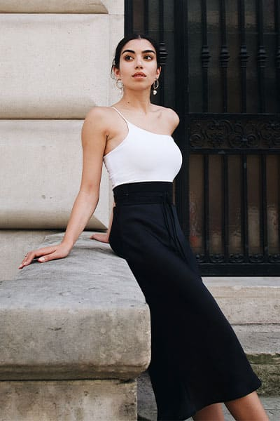 woman in one shoulder white bodysuit with black skirt and simple earrings, timeless style with neutral color blocking